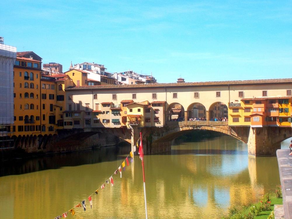 Brücke Ponte Vecchio von der Seite über dem Fluss Arno in der Alstadt von Florenz in der Toskana mit bunten Läden und Geschäften - exploreglobal