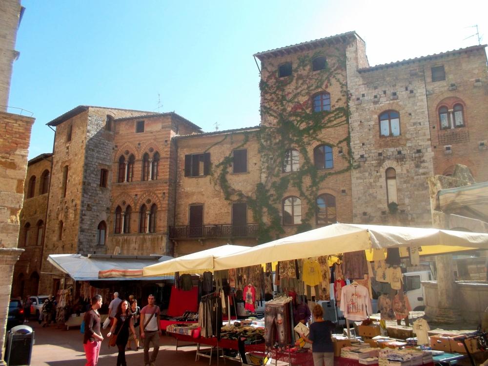 Marktplatz in der Altstadt von San Gimignano mit typischen Ständen in der Toskana - exploreglobal